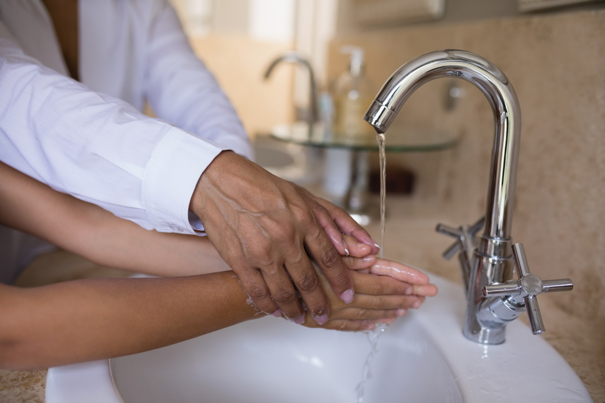 Mid section of granny helping girl while washing hands at sink